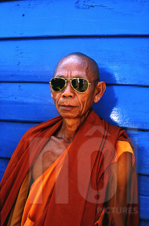 High contrast portrait of a monk wearing golden-rimmed sunglasses and traditional robe traveling on the boat between Champasack and Pakse, Laos, Southeast Asia