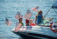 The Herrmann/Forsberg boat waves an array of American flags to celebrate along with the Winnipesaukee Yacht Club for their 4th of July boat parade on Monday morning.  (Karen Bobotas/for the Laconia Daily Sun)