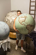 A gloge is taken from the storeroom, Bellerby and Co. Globemakers, Hackney, London, UK