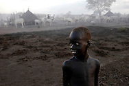 A young boy from the Mundari tribe guards cattle at a camp in Central Equatoria Province. The tribe suffered from inter-tribal conflicts and cattle rustling in the northern part of the province, so they moved further south looking for safer grazing land. The area where they settled is contaminated with unexploded ordinance and landmines. A Community Liaison Team from Mines Advisory Group (MAG) visited the tribe to survey the situation and to give mine risk education..Kuruki, South Sudan. 12/10/2009..Photo © J.B. Russell
