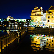 Night shot of Prague's Vltava River with reflections  on the water, Prague Castle and the Charles Bridge in the background.