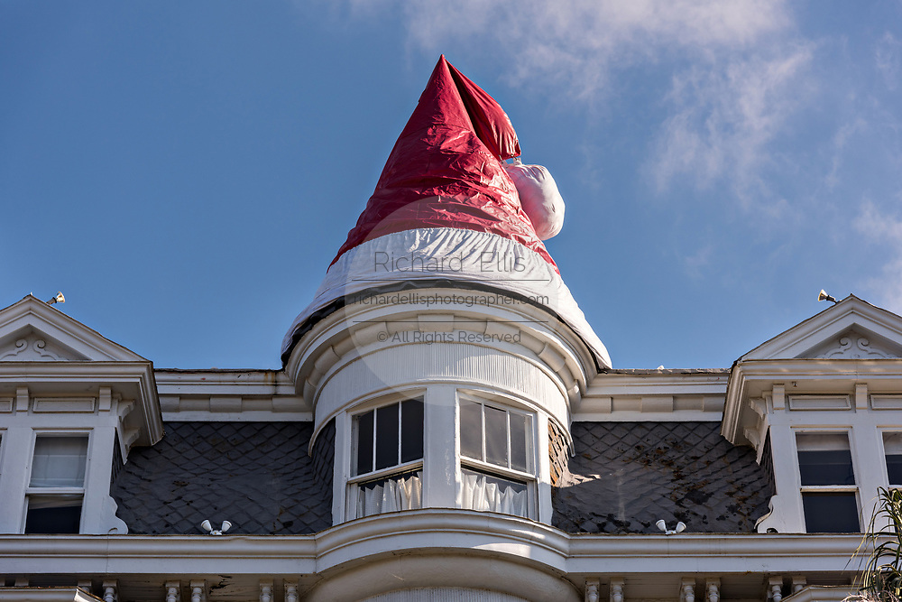 A giant Santa Hat decorates the peaked roof on a historic home decorated for Christmas on Meeting Street in Charleston, SC.