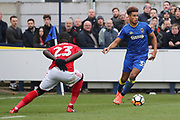 AFC Wimbledon striker Lyle Taylor (33) dribbling and taking on Charlton Athletic defender Naby Sarr (23) during the The FA Cup match between AFC Wimbledon and Charlton Athletic at the Cherry Red Records Stadium, Kingston, England on 3 December 2017. Photo by Matthew Redman.