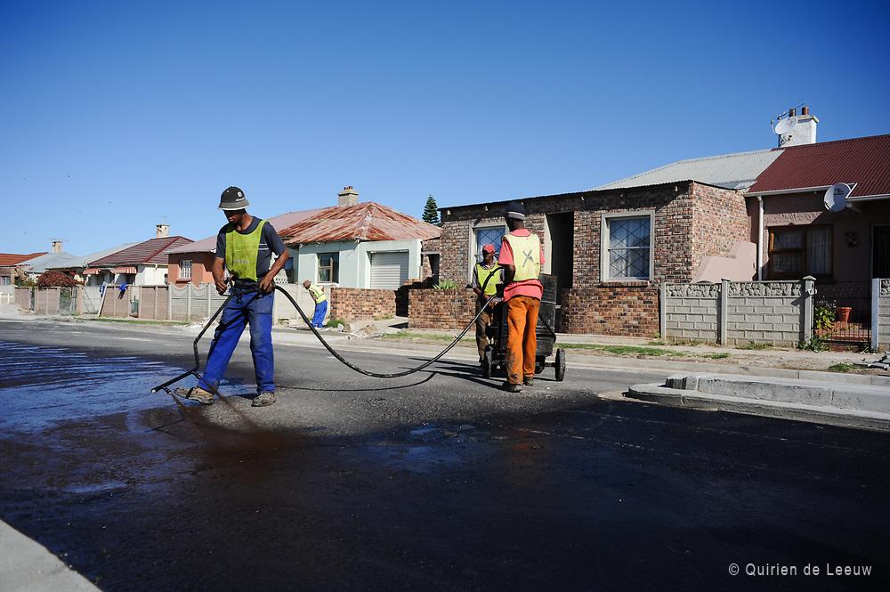 Wegwerkers teren het asfalt rond het nieuwe stadion van Port Elizabeth, WK Zuid Afrika 2010.