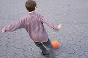 Boy in plaid shirt kicking a basket ball