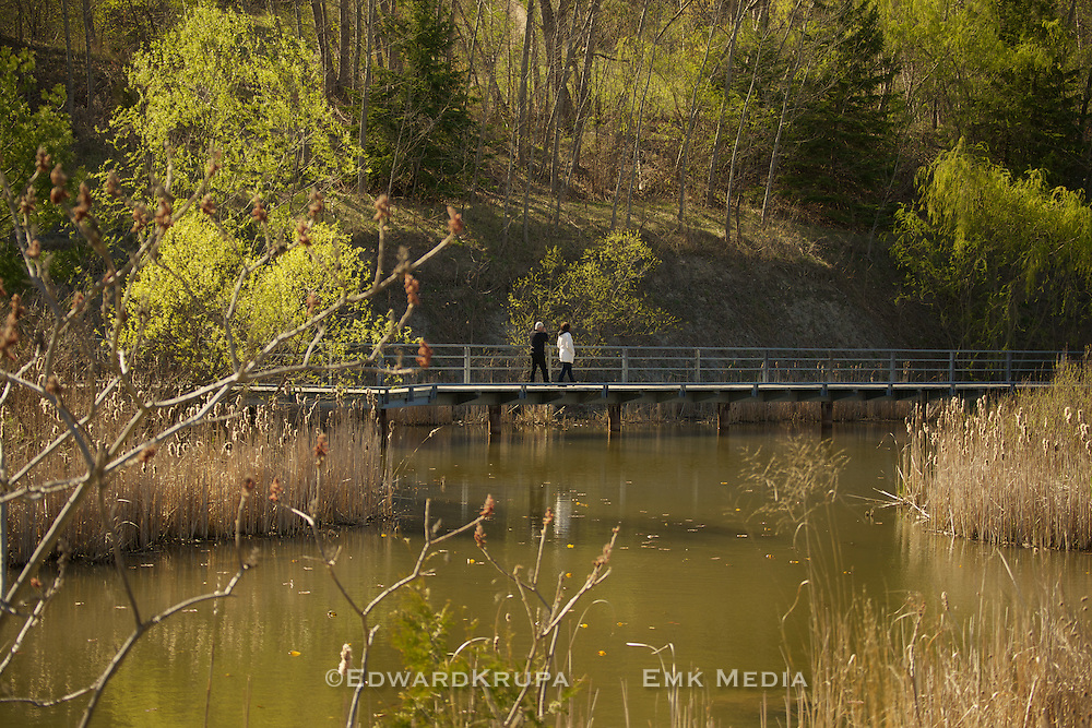 Couple walking in the Don Valley Brick Works Park part of the Evergreen Brick Works project in the springtime. Toronto, Ontario Canada.