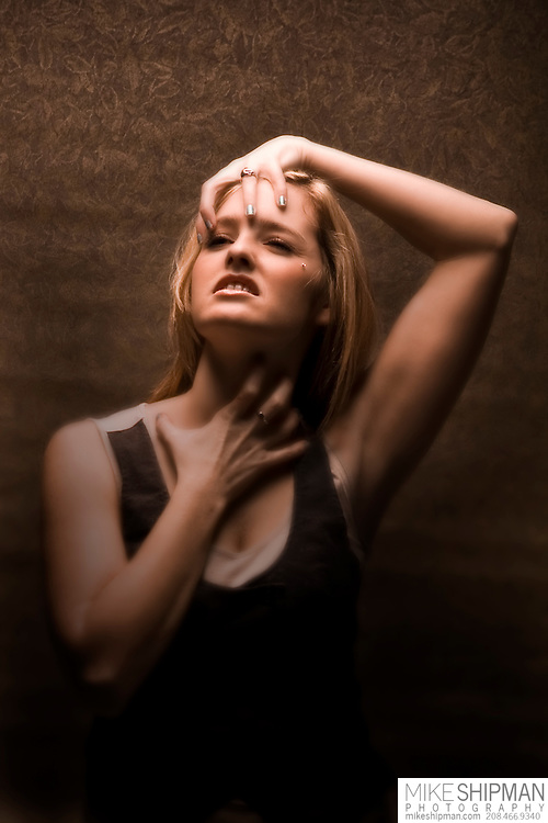 Brown toned portrait of a young woman in a black, sleeveless shirt grimacing and grabbing her head with one hand