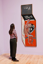 """© Licensed to London News Pictures. 06/02/2017. London, UK. A staff member views """"Tea Painting in an Illusionist Style"""" at the preview of the world's most extensive retrospective of the work of David Hockney at the Tate Britain, which will be on display 9 February to 29 May 2017. Photo credit : Stephen Chung/LNP"""