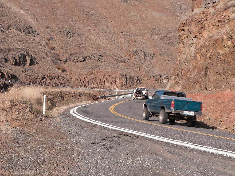 Two pickup trucks climb Rattlesnake Grade from the Grande Ronde River Canyon, Asotin County, WA, USA