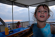 Child (5 years old) playing in back of boat at sunset, Makarska, Croatia