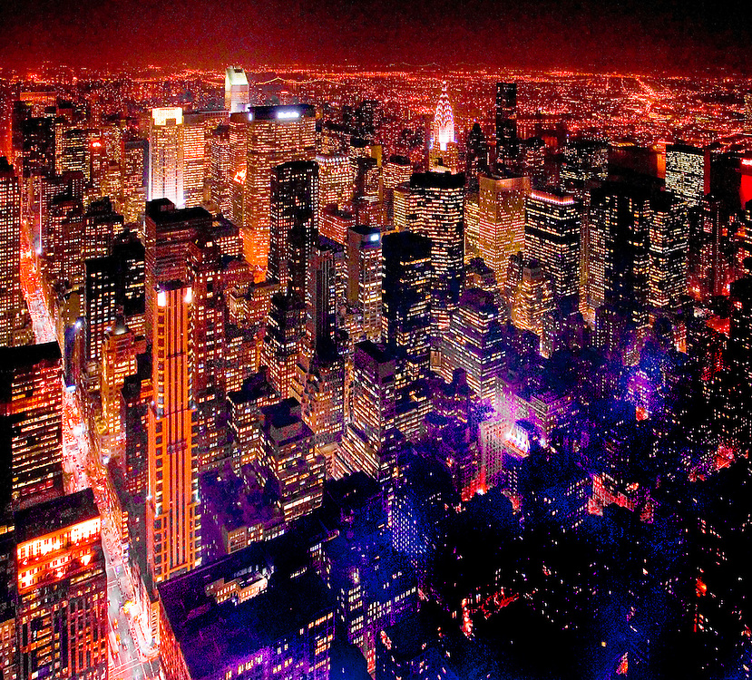 Midtown Manhattan at night from the 86th floor Observation Deck of the Empire State Building in November 2003. At left is a glittering Fifth Avenue; and the illuminated skyscraper in the background, just right of center, is the Chrysler Building.
