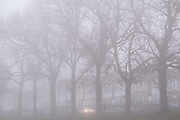 A car drives along a residential street with its headlights on to see through early morning mist, on 27th November 2020, in London, England.