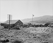 Y-480418-07. Crowds outside the longhouse at Celilo during the 1948 Feast of the First Salmon. The land surrounding the Long House is barren after being bulldozed to make room for war-surplus prefabricated houses to be moved from Madras and reassembled in Celilo Village. The entire village below the highway was going to be condemmend becasue The Dalles Dam's backwater would innundate it. Indians objected to almost every aspect of the relocation and vigouously opposed it.  April 18, 1948.