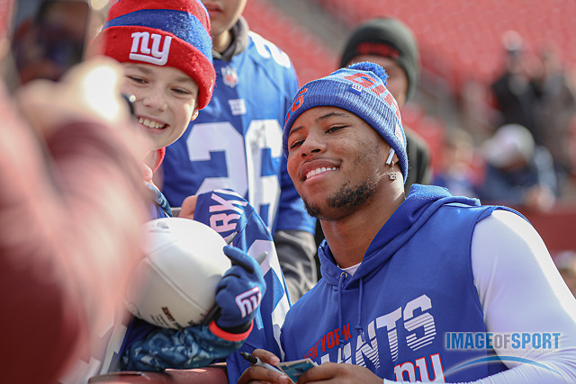 Dec 22, 2019; Landover, MD, USA; New York Giants running back Saquon Barkley (26) taking a photo with a fan prior to an NFL game against the Washington Redskins at FedEx Field. The Giants beat the Redskins 41-35. (Brian Villanueva/Image of Sport)