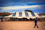 "12 JULY 2012 - FT DEFIANCE, AZ: A man walks by the main worship tent  at the 23rd annual Navajo Nation Camp Meeting in Ft. Defiance, north of Window Rock, AZ, on the Navajo reservation. Preachers from across the Navajo Nation, and the western US, come to Navajo Nation Camp Meeting to preach an evangelical form of Christianity. Evangelical Christians make up a growing part of the reservation - there are now more than a hundred camp meetings and tent revivals on the reservation every year. The camp meeting in Ft. Defiance draws nearly 200 people each night of its six day run. Many of the attendees convert to evangelical Christianity from traditional Navajo beliefs, Catholicism or Mormonism. ""Camp meetings"" are a form of Protestant Christian religious services originating in Britain and once common in rural parts of the United States. People would travel a great distance to a particular site to camp out, listen to itinerant preachers, and pray. This suited the rural life, before cars and highways were common, because rural areas often lacked traditional churches.PHOTO BY JACK KURTZ"