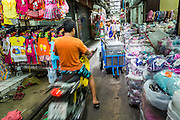 06 JUNE 2013 - BANGKOK, THAILAND:     A motorcycle passes a food pushcart in Bobae Market in Bangkok. Bobae Market is a 30 year old market famous for fashion wholesale and is now very popular with exporters from around the world. Bobae Tower is next to the market and  advertises itself as having 1,300 stalls under one roof and claims to be the largest garment wholesale center in Thailand.       PHOTO BY JACK KURTZ