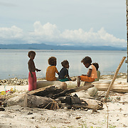 Papua kids playing in the shade of a coconut tree on the white sandy beach.