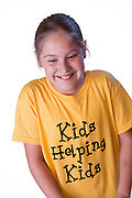 An individual child wearing a yellow t-shirt, smiling and looking happy.