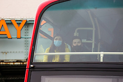 © Licensed to London News Pictures. 02/03/2021. London, UK. A couple wearing protective face coverings travelling on a bus in north London. The number of Covid-19 infection rate and deaths have dropped more than a quarter within a week as the effect of lockdown restrictions and vaccine rollout is making an impact. Six cases of the P1 variant have been identified in people who recently returned from Brazil. Photo credit: Dinendra Haria/LNP