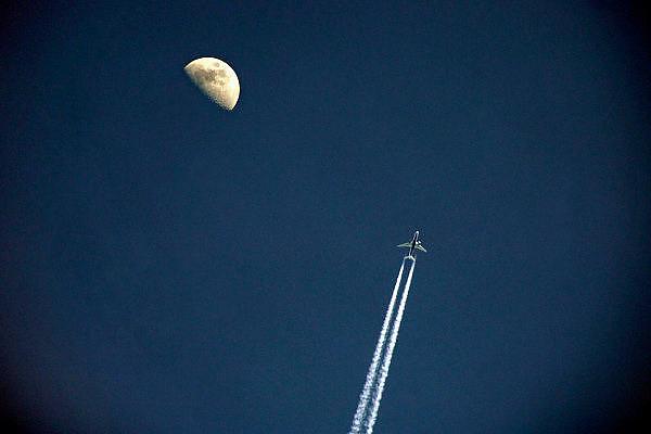 Nederland, Nijmegen, 26-3-2007..Een vliegtuig trekt strepen, condensatie, in de blauwe lucht met de halve maan op de achtergrond. ..Foto: Flip Franssen/Hollandse Hoogte