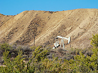 A natural gas well pump located in the Douglas Creek valley of Blanco County south of Rangely, Colorado, USA with ATV tracks on a hillside in the background.