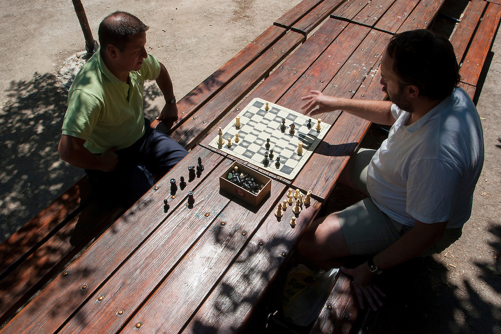 Two men enjoy a pleasant Sunday morning playing chess at Parque del Retiro in madrid, Spain.