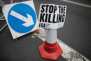 """A sign reading ' Stop the Killing""""  by Friends of Al-Aqsa has been added to a traffic cone with a street sign arrow pointing at it.<br /> <br /> Tens of thousands of protesters marched in Central London to show their outrage against the Israeli onslaught on Gaza."""