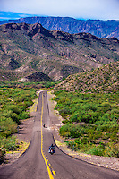 Motoryclists ride down a long straight road (FM 170, the Camino del Rio), Big Bend Ranch State Park, Texas USA.