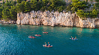 Aerial view of group of kayakers paddling near cliffs in Zivogosce, Dalmatia, Croatia.