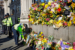 © Licensed to London News Pictures. 25/03/2017. London, UK. Police officers pay their respects to the victims of Westminster terror attack outside the Houses of Parliament in London on 25 March 2017. Photo credit: Tolga Akmen/LNP