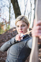 Young woman shooting with bow and arrow