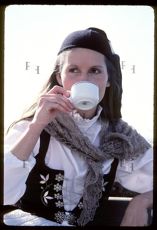 Signy Kjartansdottir, a guide at Arbaer Folk Museum dressed in nat'l costume, sips her coffee. Iceland