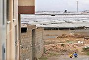 Spanje, El Ejido, 10-11-2019In dit deel van Andalucie worden veel groenten en fruit verbouwd die hun weg vinden via de export naar o.a. Nederland . Het wordt de zee van plastic genoemd omdat de kassen opgebouwd zijn van houten of metalen palen bedekt met zwaar plastic. In de kassen werken voornamelijk migranten uit Afrika, en arbeidsmigranten uit Oost-Europa die een laag loon uitbetaald krijgen, tussen de 30 en 40 euro per 8 urige dag, werkdag, afhankelijk van de werkgever. Er wordt door de kaseigenaren en transportbedrijven goed verdiend maar de boeren vinden dat ze teveel negatieve aandacht krijgen in de media in noord-europa. De populistische partij Vox heeft hier een grote aanhang. Kinderen spelen aan de rand van de stad waar meteen de kassen staan.Foto: Flip Franssen