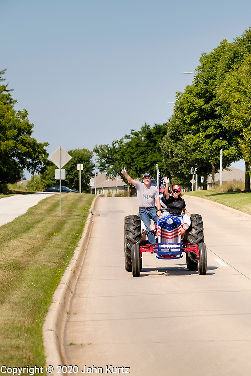 """08 AUGUST 2020 - WEST DES MOINES, IOWA: GARY LEFFLER, from West Des Moines, and TANA GOERTZ, drive a red, white, and blue tractor down Mills Civic Parkway during a rally to support law enforcement in West Des Moines. About 100 people gathered at the West Des Moines Law Enforcement Center to rally in support of law enforcement. The rally was organized by """"Uplifting Our Police,"""" a local organization that supports law enforcement. They rallied at Des Moines Police headquarters in July. They are planning similar rallies at police stations in the Des Moines metropolitan area.      PHOTO BY JACK KURTZ"""
