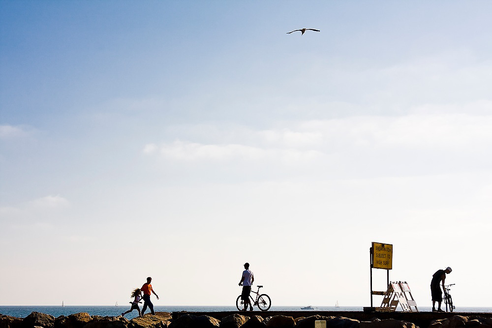 A father, daughter and two friends with bicycles walk along the boardwalk at Dana Point, California.