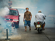 02 DECEMBER 2015 - BANGKOK, THAILAND:   People walk through the fog of chemicals used to kill mosquitoes during a dengue fever prevention mission in central Bangkok. The Public Health Ministry in Thailand said that more than 111,000 cases of dengue fever have been reported in 2015, an increase of more than 200% over the number of cases of dengue fever reported 2014. Dengue fever is a virus spread by mosquito and is endemic in southeast Asia. Thai health officials are aggressively spraying areas where mosquitoes are known to live and leading public information and education sessions on preventing dengue fever. There is no vaccine for dengue fever, so preventing dengue means avoiding mosquitoes.      PHOTO BY JACK KURTZ