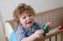 Baby boy holding a toy and crying to be taken out of his cot,