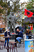 Men sit outside drinking and smoking next to the Albanian flag and a statue of  Mehë Uka in the shopping area in the south side of Mitrovica, a town in Northern Kosovo that straddles the river Ibar that separates the Serbian and Albanian districts of Mitrovica, Kosovo on the 12th of December 2018.  Meha Uka was a teacher, political prisoner, who is  a Hero of Kosovo. Mitrovica or Kosovska Mitrovica is a city and municipality located in Northern Kosovo.  (photo by Andrew Aitchison / In pictures via Getty Images)