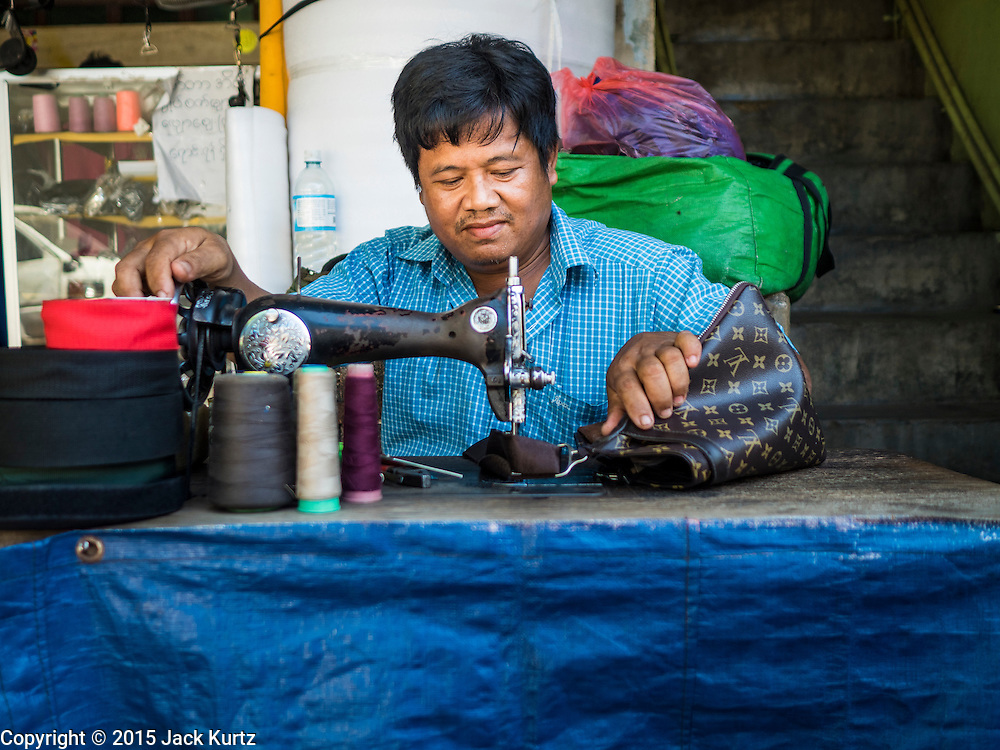 """06 NOVEMBER 2015 - YANGON, MYANMAR: A man repairs luggage at his street stall with a treadle powered sewing machine. Some economists think Myanmar's informal economy is larger than the formal economy. Many people are self employed in cash only businesses like street food, occasional labor and day work, selling betel, or working out of portable street stalls, doing things like luggage repair. Despite reforms in Myanmar and the expansion of the economy, most people live on the informal economy. During a press conference this week, Burmese opposition leader Aung San Suu Kyi said, """"a great majority of our people remain as poor as ever.""""  PHOTO BY JACK KURTZ"""