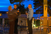 Guests on the terrace (unsharp blurred) having aperitif drinks before dinner in the evening with the dark blue sky and sea in the background Clos des Iles Le Brusc Six Fours Cote d'Azur Var France