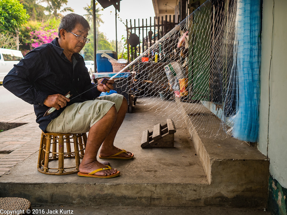 """13 MARCH 2016 - LUANG PRABANG, LAOS: A man repairs his fishing nets in front of his home in Luang Prabang. Scenes like this, once common in the town, are now rare because so many working class Lao people have sold their homes to real estate speculators and moved out of town. Luang Prabang was named a UNESCO World Heritage Site in 1995. The move saved the city's colonial architecture but the explosion of mass tourism has taken a toll on the city's soul. According to one recent study, a small plot of land that sold for $8,000 three years ago now goes for $120,000. Many longtime residents are selling their homes and moving to small developments around the city. The old homes are then converted to guesthouses, restaurants and spas. The city is famous for the morning """"tak bat,"""" or monks' morning alms rounds. Every morning hundreds of Buddhist monks come out before dawn and walk in a silent procession through the city accepting alms from residents. Now, most of the people presenting alms to the monks are tourists, since so many Lao people have moved outside of the city center. About 50,000 people are thought to live in the Luang Prabang area, the city received more than 530,000 tourists in 2014.    PHOTO BY JACK KURTZ"""