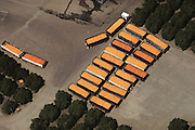 Aerial photograph of truck trailers full of just-harvested oranges and grapefruits ready to be made into juice at this Lindsay, California citrus juice factory. San Joaquin Valley. The factory is surrounded by orange trees. USA.