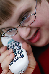 Teenage Downs Syndrome boy using a large button telephone,
