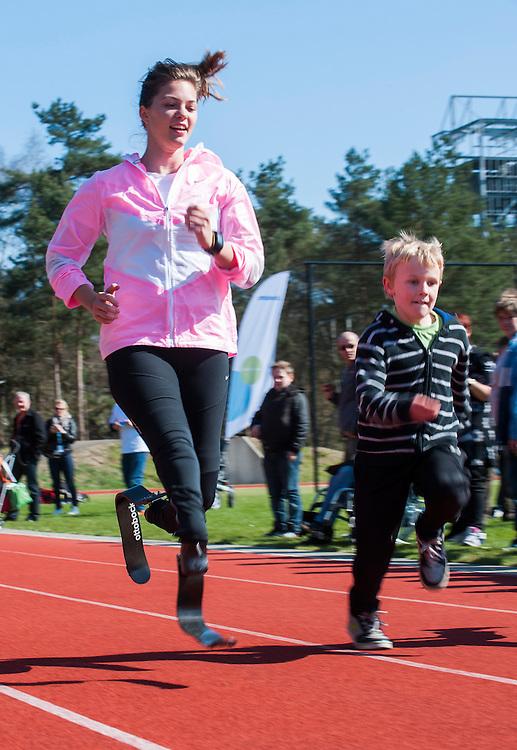 Nederland, Doorn, 20 april 2013<br /> Het Militair Revalidatie Centrum (MRC) organiseerde een prothese sportdag met clinics door olympische sporters voor mensen met een prothese. De sportdag vond plaats in de Van Braam Houckgeestkazerne in Doorn onder het motto 'Sporten met een prothese: gewoon doen' <br /> Blade babe Marlou van Rhijn rent tegen een jongetje<br /> Foto(c): Michiel Wijnbergh