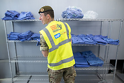 © Licensed to London News Pictures. 13/04/2020. Manchester, UK. A soldier from the 1st Battalion the Duke of Lancaster's Regiment helps to unpack scrubs . The National Health Service has built a 648 bed field hospital for the treatment of Covid-19 patients , at the historical railway station terminus which now forms the main hall of the Manchester Central Convention Centre . The facility is due to open this week (commencing Easter Monday , 13th April 2020 ) and will treat patients from across the North West of England , providing them with general medical care and oxygen therapy after discharge from Intensive Care Units . Photo credit: Joel Goodman/LNP