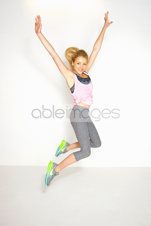 Young Woman in Sportswear Jumping with Arms Raised