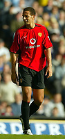 Photo. Aidan Ellis.<br />Leeds United v Manchester United.<br />FA Barclaycard Premiership.<br />18/10/2003.<br /> Manchester's Rio Ferdinand smiles at the Leeds Kop end as the fans give him abuse