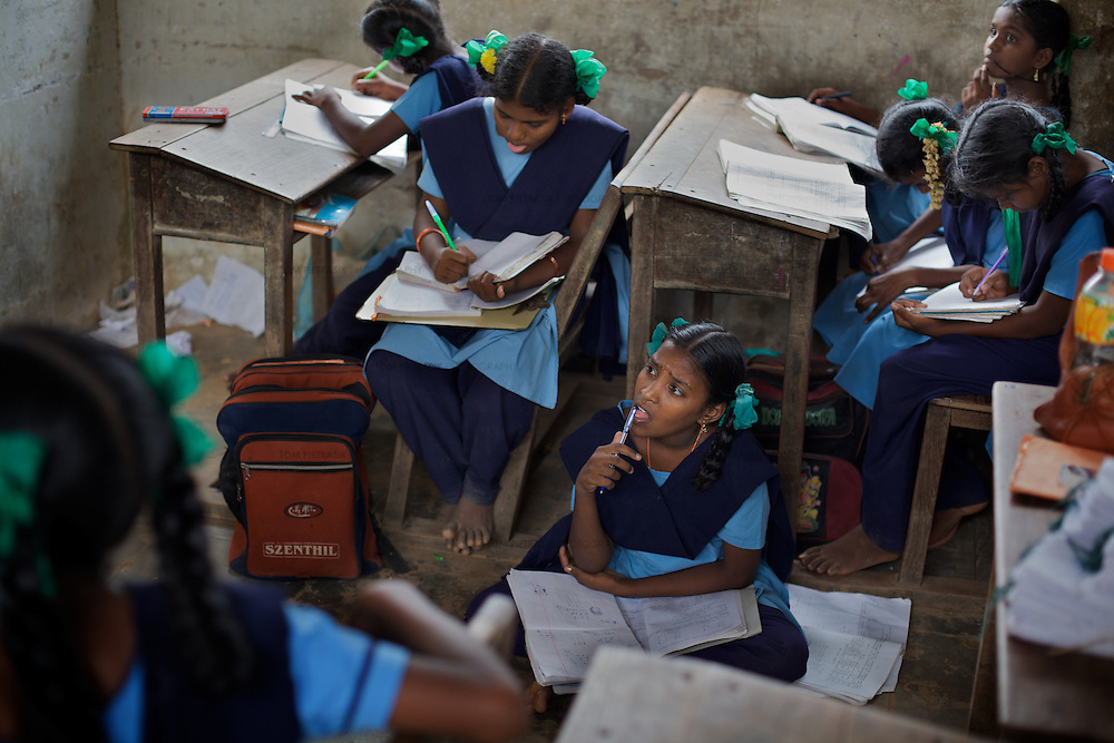 """Pupils at the Government Girls High School, Venugopalapuram, Cuddalore...Cuddalore's Government Girls High School is under-resourced with some student forced to sit on the floor for want of a desk. Though most classrooms are housed in a building that is only two years old, there is little ventilation to lessen the effects Cuddalore's tropical heat. The school does offer extra """"`bridge"""" classes for those students recently arrived from village schools but staff are frequently absent from the school...Photo: Tom Pietrasik.Cuddalore town, Tamil Nadu. India.October 5th 2009"""