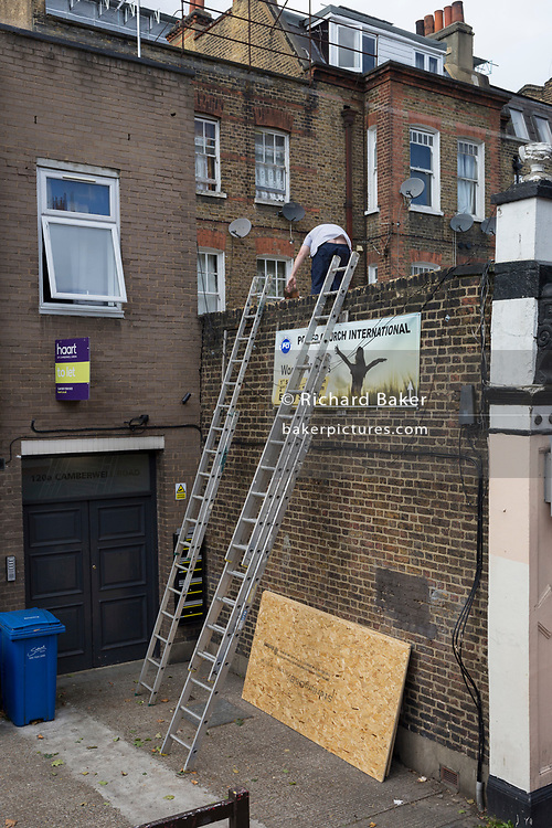 A workman bends down while working on a Christian church on the Walworth Road, on 14th September 2017, in London, England.