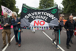 Environmental activists from Stop the Silvertown Tunnel take part in an Extinction Rebellion Stop The Harm march during the fourth day of Impossible Rebellion protests on 26th August 2021 in London, United Kingdom. Extinction Rebellion are calling on the UK government to cease all new fossil fuel investment with immediate effect.